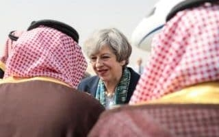 Theresa May speaks with members of the welcoming delegation after her arrival in Riyadh in April