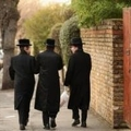 Jewish men walk along the street in the Stamford Hill area of north London on January 19, 2011 in London, England